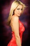 Reizvolles blondes Frauenart und weisebaumuster im roten Kleid Stockbild