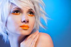 Reizvolles blondes Frauenportrait auf Blau Lizenzfreie Stockbilder