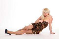 Reizvolles blondes Frauensitzen des Fußbodens im kurzen Kleid Lizenzfreies Stockfoto