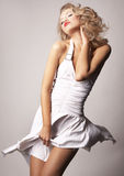 Reizvolles blondes Mädchen auf grauem Hintergrund Lizenzfreie Stockfotos