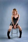 Reizvolles blondes Mädchen, das auf Stuhl sitzt Stockbild