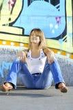 Reizvolles blondes Mädchen nahe Farbenwand lizenzfreie stockbilder