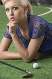 Reizvolles blondes Mädchen zahlt Golf mit der Hand Lizenzfreies Stockbild