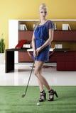 Reizvolles blondes Mädchen zahlt Golf, schaut innen zum Objektiv Stockfotos