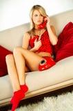 Reizvolles blondes Mädchen mit rotem Telefon Lizenzfreies Stockfoto