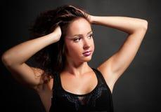 Reizvolles Brunettemädchen auf dunklem Hintergrund lizenzfreies stockbild