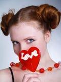 Reizvolles hübsches Mädchen mit rotem Lutscher Lizenzfreie Stockfotografie