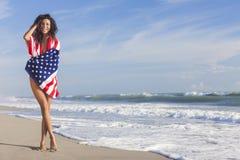 Reizvolles junge Frauen-Mädchen in der amerikanischen Flagge auf Strand Stockfoto