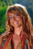 Reizvolles junges Mädchen, das auf grünem Hintergrund lächelt Stockbild