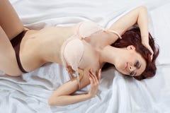 Reizvolles junges Mädchen der Schönheit auf Seide ziehen Büstenhalter aus Lizenzfreie Stockfotos