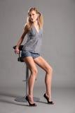 Reizvolles langes mit Beinen versehenes blondes Baumuster, das auf Stabschemel sitzt Stockbild