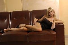 Reizvolles Mädchen auf einem Sofa Lizenzfreie Stockfotos