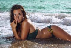 Reizvolles Mädchen, das auf dem Strand liegt Stockbild