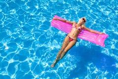 Reizvolles Mädchen, das auf eine Matratze im Meer schwimmt Lizenzfreie Stockfotos