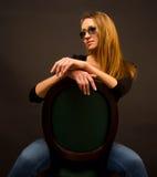 Reizvolles Mädchen, das auf einem Stuhl sitzt Lizenzfreie Stockfotografie