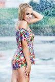 Reizvolles Mädchen, das entlang nasse Straße nach Regen geht Stockfotografie