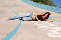 Reizvolles Mädchen, das Mädchen, das auf einer Betonplatte liegt stockfoto