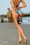 Reizvolles Mädchen, das rückseitige Champagnerflasche versteckt Lizenzfreie Stockbilder