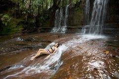 Reizvolles Mädchen, das sich im Fluss hinlegt Stockbild