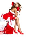 Reizvolles Mädchen, das Weihnachtsmann-Kleidung trägt Stockfotos