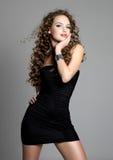 Reizvolles Mädchen des jungen Zaubers im schwarzen Kleid Stockfotografie