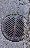 Rejilla de la alcantarilla en asfalto Fotografía de archivo