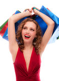 Rejoicing girl in red dress with purchases Royalty Free Stock Photo
