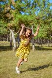 Rejoicing happy little girl. In flying motion smiling full of joy and vitality in summer or spring forest Royalty Free Stock Images
