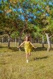 Rejoicing happy little girl. In flying motion smiling full of joy and vitality in summer or spring forest Stock Photos