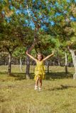 Rejoicing happy little girl. In flying motion smiling full of joy and vitality in summer or spring forest Royalty Free Stock Image