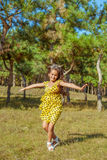 Rejoicing happy little girl. In flying motion smiling full of joy and vitality in summer or spring forest Royalty Free Stock Photography