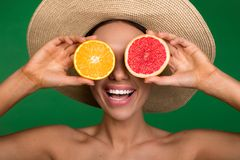 Glad girl with fruit instead of eyeballs. Rejoicing lady with hat on her head and nude upper body covering eyes with dissected fruits. Isolated on background Royalty Free Stock Photography