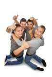 Rejoicing togheter. Four young friends knelt rejoicing for their success Royalty Free Stock Photos
