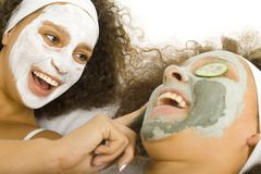 Rejuvenescent treatment. Happy young women lying on towel putting green puryfing mask Royalty Free Stock Images