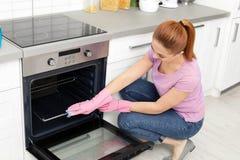 Rek van de vrouwen het schoonmakende oven met vod stock foto's