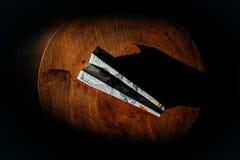 $ 100 rekening in de vorm van een vliegtuig die op een houten cirkel liggen het vliegtuig wordt gemaakt van bankbiljetten stock afbeelding