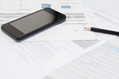 Rekening en slimme telefoon met potlood Stock Afbeelding