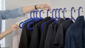 Rekhoogtepunt van zwarte kleren De vrouw hangt verschillende types van zwarte kleren op een rek stock video