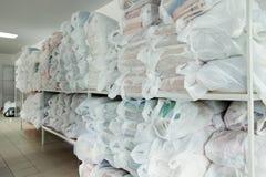Rekken met schoon linnen in wasserijruimte Royalty-vrije Stock Afbeeldingen