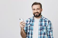 Reklama i technologii pojęcie Przystojny europejski samiec modela mienia smartphone w ręce podczas gdy ono uśmiecha się cheerfuly obrazy stock