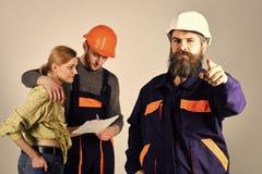 Rekrutacyjny pojęcie Brygada pracownicy, budowniczowie w hełmach, naprawiacze i dama dyskutuje kontrakt, popielaty tło obraz royalty free