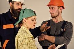Rekrutacyjny pojęcie Brygada pracownicy, budowniczowie w hełmach, naprawiacze i dama dyskutuje kontrakt, popielaty tło fotografia stock
