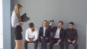Rekruten die op gesprekken voor werkgelegenheid wachten een groep die jonge zakenman op het begin van de ontvangst wachten stock foto's