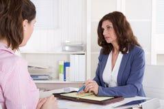 Rekrytering: kvinna för affär som två i regeringsställning sitter. arkivfoton