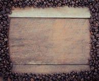 Rektangelram som göras av kaffebönor på träbakgrunden Arkivfoto