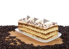 Rektangulär formad Tiramisu på plattan som omges av kaffebönor royaltyfri bild