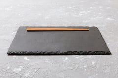 Rektangulärt kritisera plattan med pinnar för sushi på svart marmorbakgrund royaltyfri foto