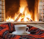 Relájese con la taza de té antes de chimenea acogedora Imagen de archivo
