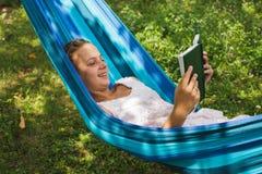 Relájese con un libro en el jardín verde Imágenes de archivo libres de regalías