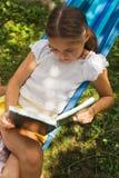 Relájese con un libro en el jardín verde Imagenes de archivo